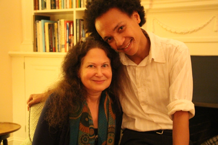 Clear and Jane Hirshfield posing for a picture. she is seated and he is leaning on the arm of the seat with his arm around her.