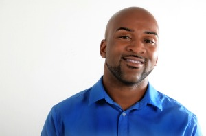 Headshot of Drew Anderson, a handsome Black man with a trimmed beard clean shaved head. He is wearing a royal blue button-up shirt and looking directly into the camera.