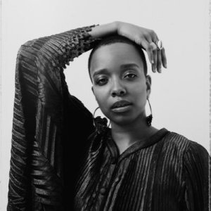 Black and white photo of Jamila Woods posing with her hand resting atop her head.