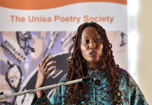 Action photo of Natalia Molebatsi speaking in front of a mic with her hand raised slightly gesticulating. She's wearing a light green top and her locs are draping down over her shoulders. A sign behind her says The Unisa Poetry Society.